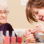 Image of elderly woman receiving a manicure