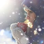 Image of woman sipping hot drink on snowy day