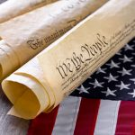 Image of rolled-up Constitutions and American flag