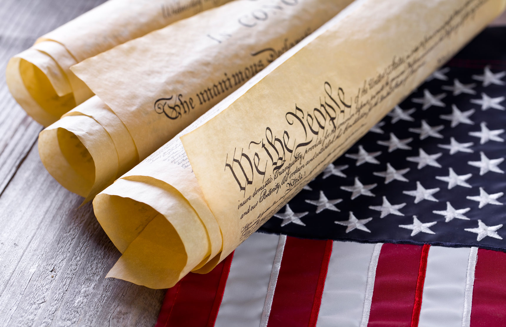 Image of Declaration of Independence Rolled Up lying on an American Flag