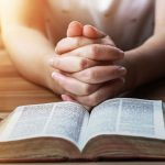 Image of Hands Clasped Together Behind Open Bible